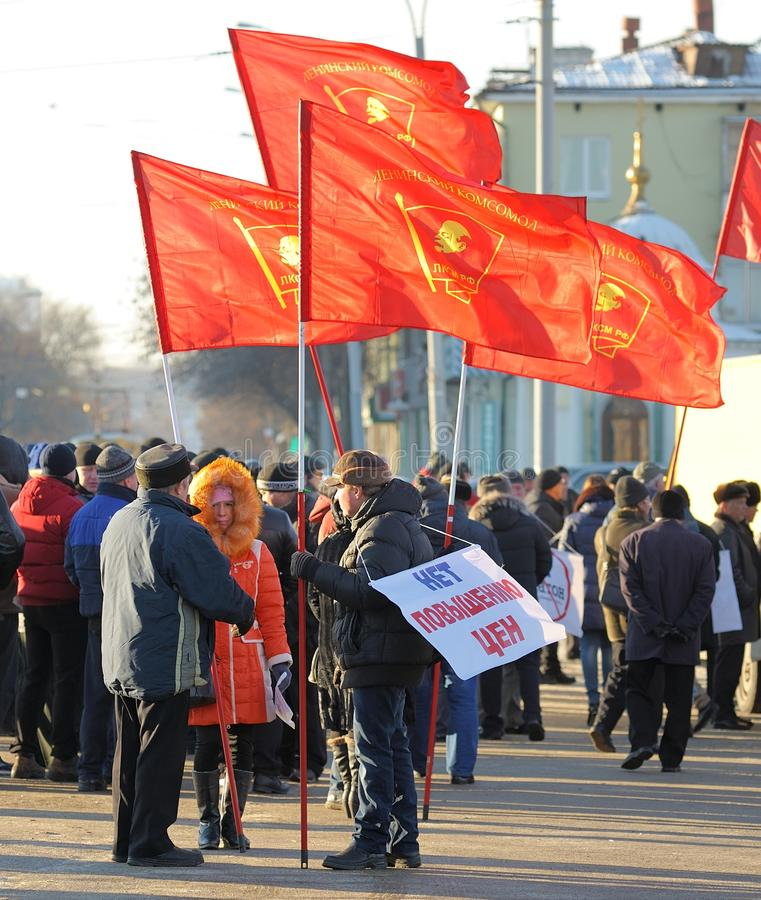 Orel, Russia - November 29, 2015: Russian truck drivers protest. Strikers with red communist flags. No to price rise sign on striker's back on street royalty free stock photography