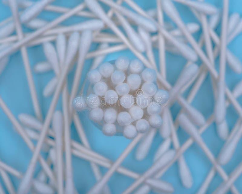 Orelha algodão-derrubada branca da extremidade dobro orgânica e para compor os cotonetes, botões no azul fotografia de stock royalty free
