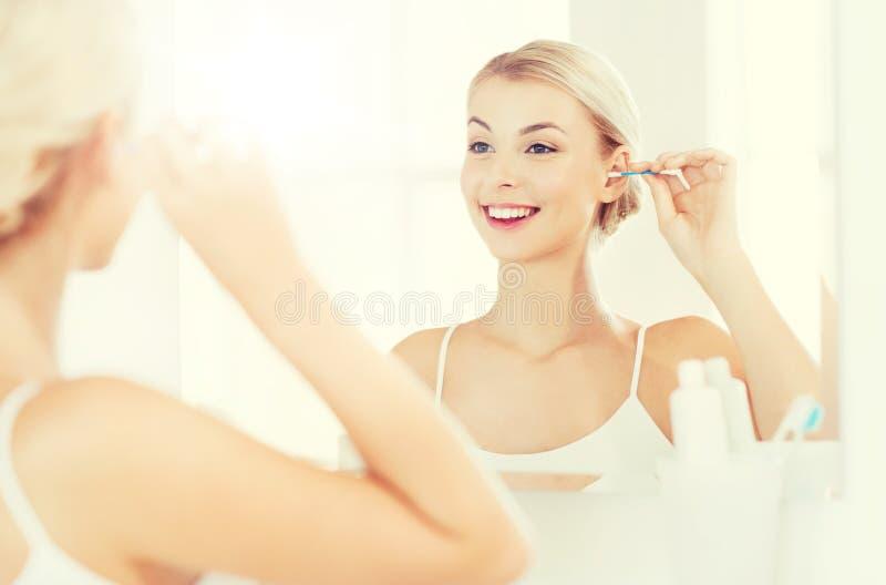 Orelha da limpeza da mulher com o cotonete de algodão no banheiro foto de stock royalty free