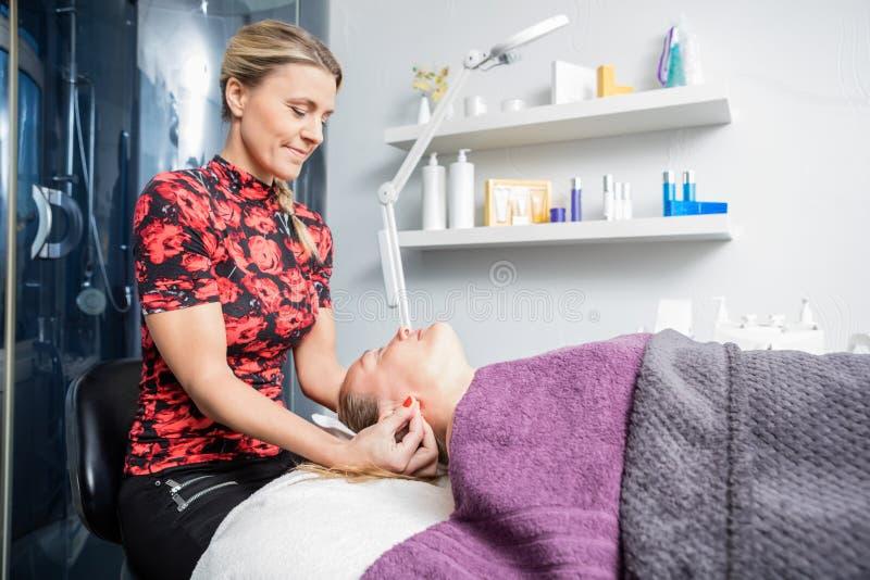 A orelha de Massaging Female Customer do esteticista fotografia de stock royalty free