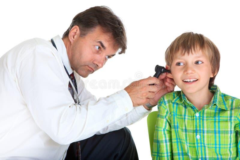 Orelha do menino de exame do doutor fotografia de stock royalty free