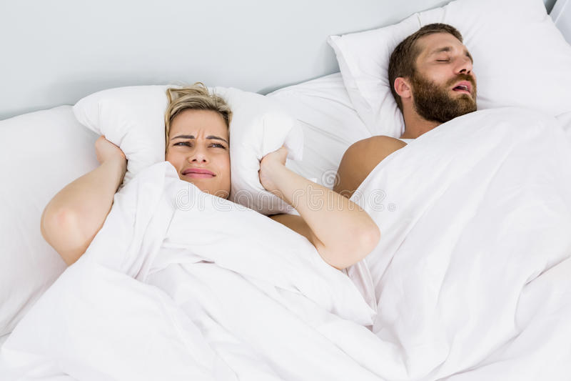 Orelhas da coberta da mulher quando homem que ressona na cama imagens de stock