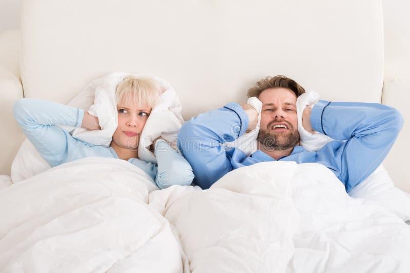 Orelhas da coberta dos pares ao dormir na cama imagens de stock royalty free