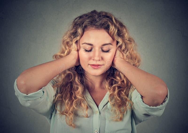 Orelhas da coberta da jovem mulher que evitam o ruído no fundo cinzento foto de stock