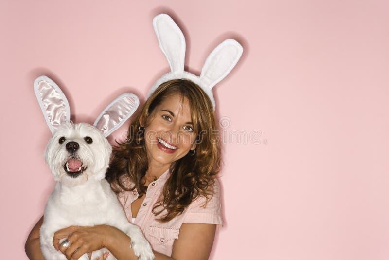 Orelhas de coelho desgastando da mulher e do cão branco. imagem de stock royalty free
