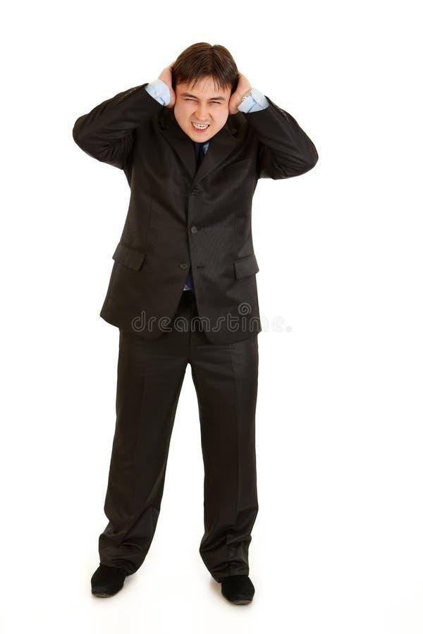 Orelhas de fechamento irritadas do homem de negócios com mãos fotos de stock royalty free