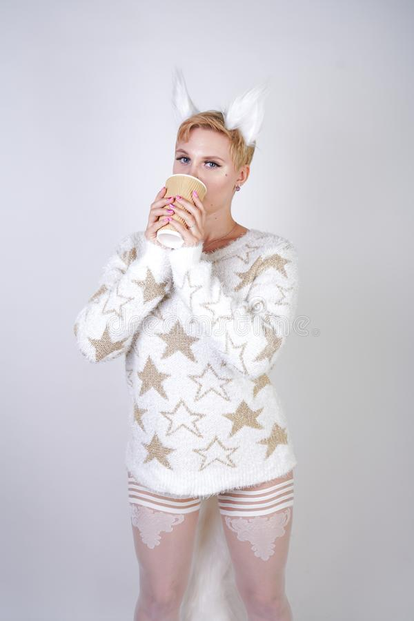 Orelhas de gato mornas feitas malha da camiseta e da pele do wearng da mulher do tamanho forma caucasiano positiva bonita e levan fotos de stock