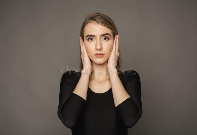 Orelhas destacadas da coberta da mulher com mãos imagem de stock royalty free