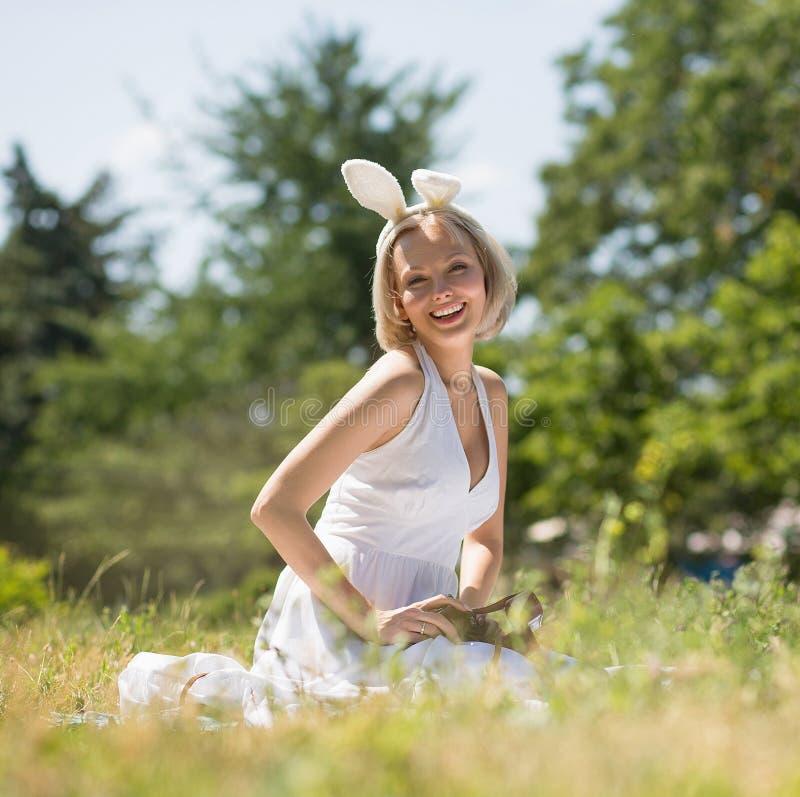 Orelhas vestindo do coelho da mãe nova feliz, assento de sorriso na cobertura fora fotografia de stock
