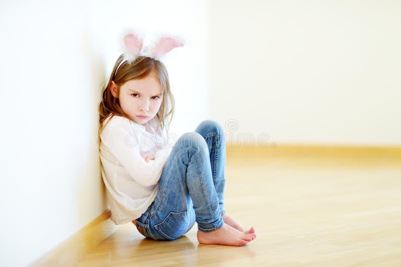 Orelhas vestindo do coelho da menina muito irritada que sentam-se em um assoalho imagens de stock royalty free