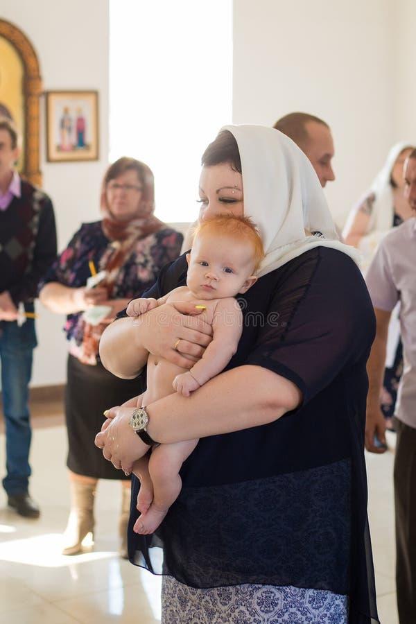 Orenburg, Federation-2 russo Aprel 2019 Donna che tiene un bambino durante il rituale di battesimo fotografia stock libera da diritti