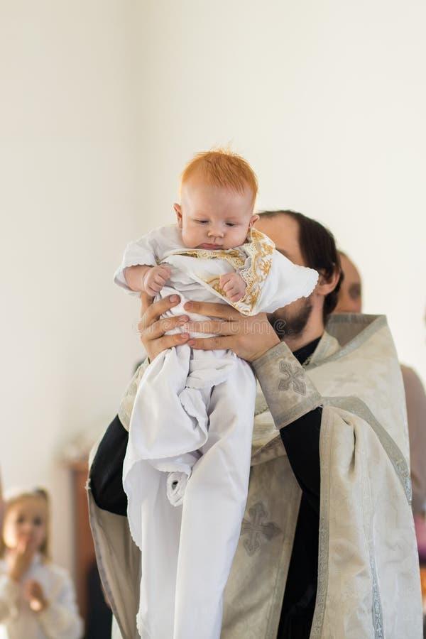 Orenburg, Federation-2 russo Aprel 2019 Sacerdote ortodosso che tiene un bambino durante il rituale di battesimo fotografie stock libere da diritti
