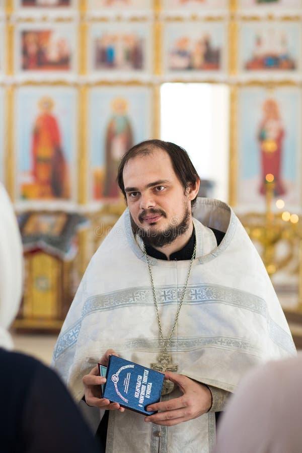 Orenburg, Federation-2 russo Aprel 2019 Un giovane sacerdote ortodosso tiene un certificato di battesimo in sue mani fotografie stock libere da diritti
