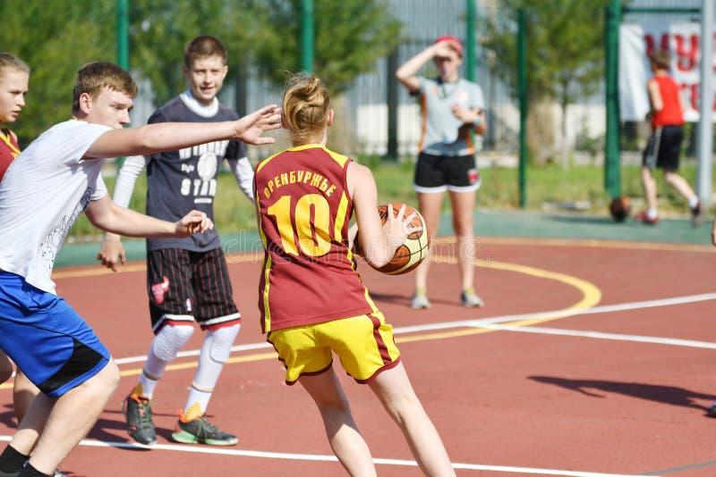 Orenburg, Rússia - 30 de julho de 2017 ano: Basquetebol da rua do jogo das meninas e dos meninos fotografia de stock