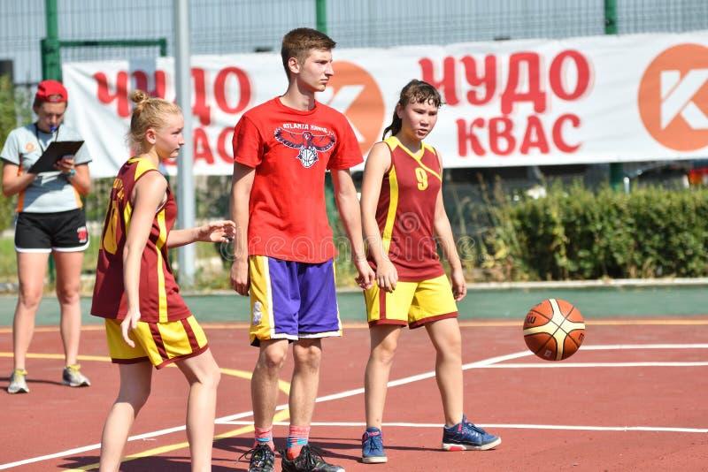 Orenburg, Rússia - 30 de julho de 2017 ano: Basquetebol da rua do jogo das meninas e dos meninos imagem de stock