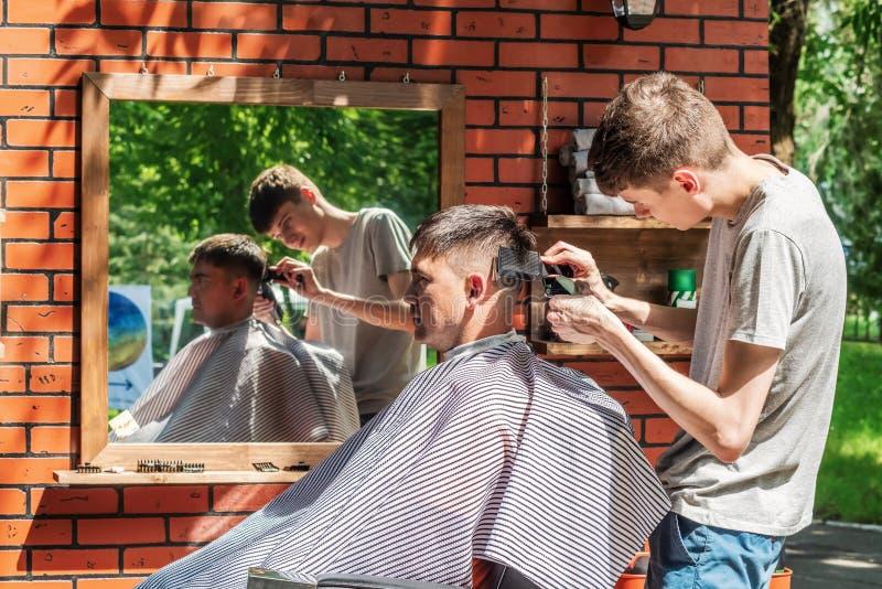 Hairdresser cuts a man in an open air salon stock image
