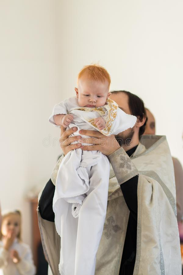 Orenburg, Russian Federation-2 Aprel 2019. Orthodox priest holding a baby during the baptism ritual. On the background of the altar royalty free stock photos