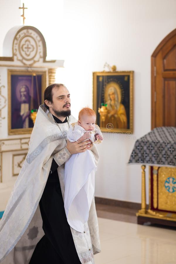 Orenburg, Russian Federation-2 Aprel 2019. Orthodox priest holding a baby during the baptism ritual. On the background of the altar royalty free stock photo