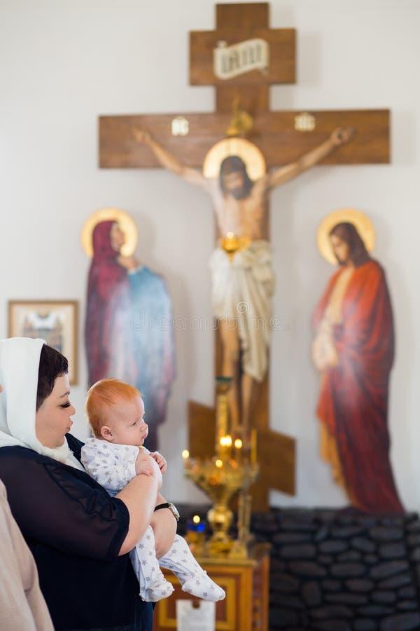 Orenburg, russisches Federation-2 Aprel 2019 Frau, die ein Baby auf dem Hintergrund eines orthodoxen Kreuzes hält stockbilder