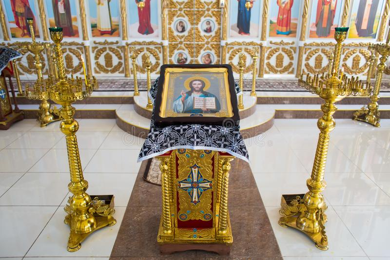 Orenburg, russisches Federation-2 Aprel 2019 Ikone von Jesus Christ der Allmächtiger auf einem vergoldeten Stand nahe bei Kerzen lizenzfreies stockbild