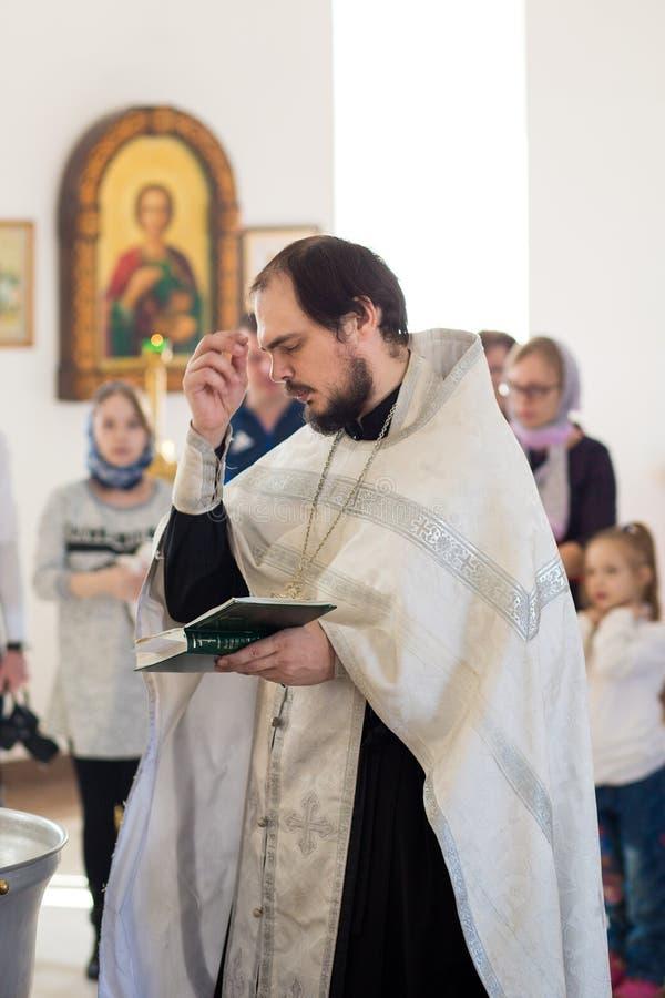 Orenburg, russisches Federation-2 Aprel 2019 Junger orthodoxer während der Liturgie getauft zu werden Priester, stockbild
