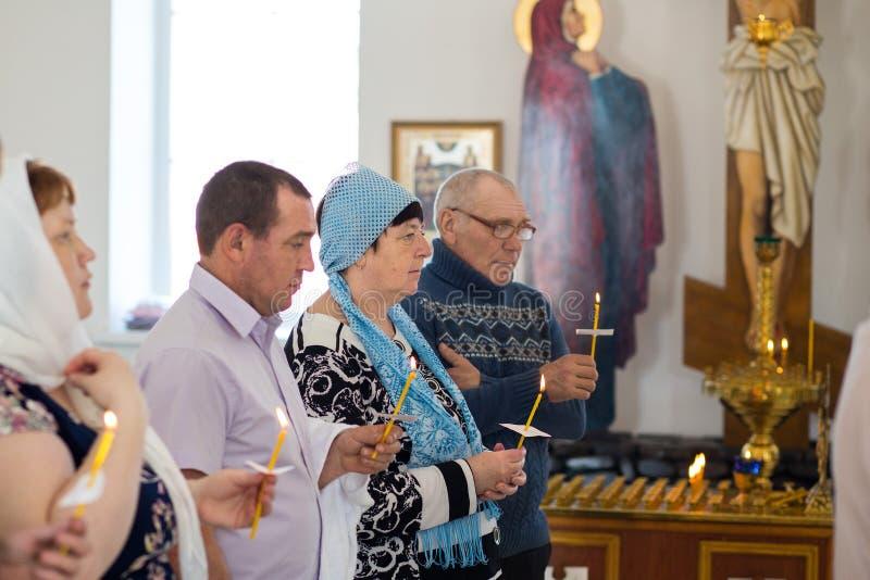 Orenburg, russisches Federation-2 Aprel 2019 Leute halten Kerzen während des Rituals der Taufe in der orthodoxen Kirche lizenzfreies stockbild