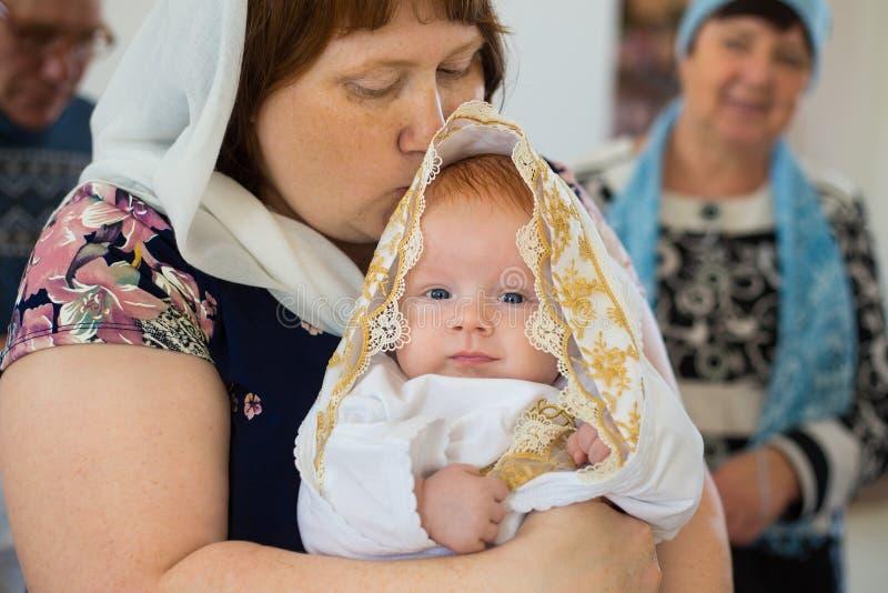 Orenburg, russo Federation-2 Aprel 2019 Mulher que guarda um bebê durante o ritual do batismo foto de stock