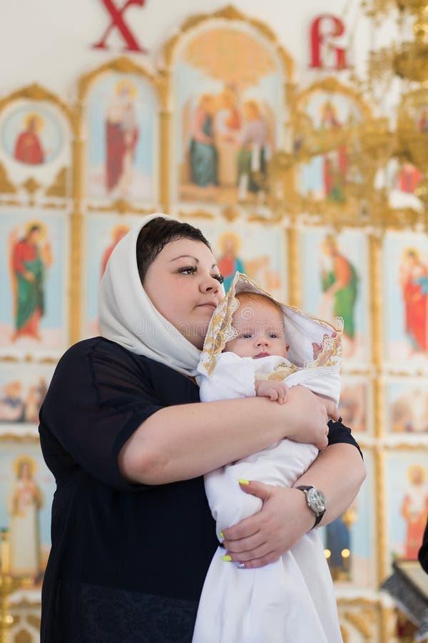 Orenburg, russo Federation-2 Aprel 2019 Mulher que guarda um bebê durante o ritual do batismo imagem de stock