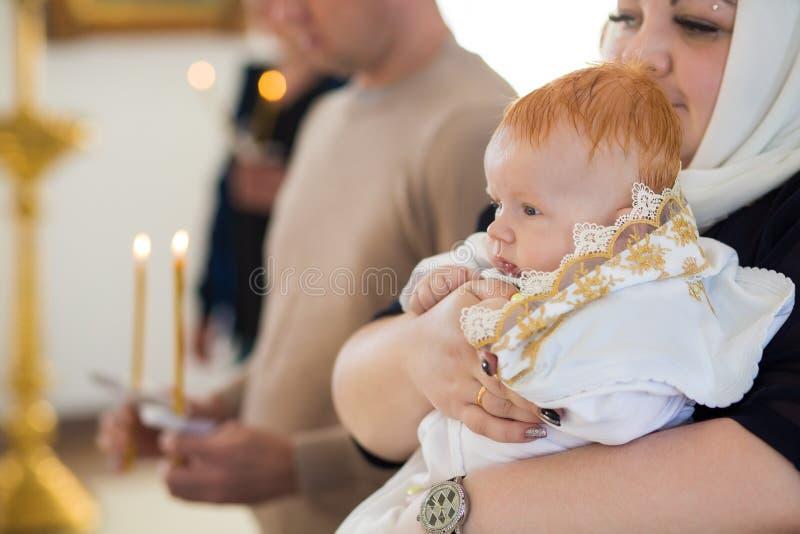 Orenburg, russo Federation-2 Aprel 2019 Mulher que guarda um bebê durante o ritual do batismo fotos de stock royalty free
