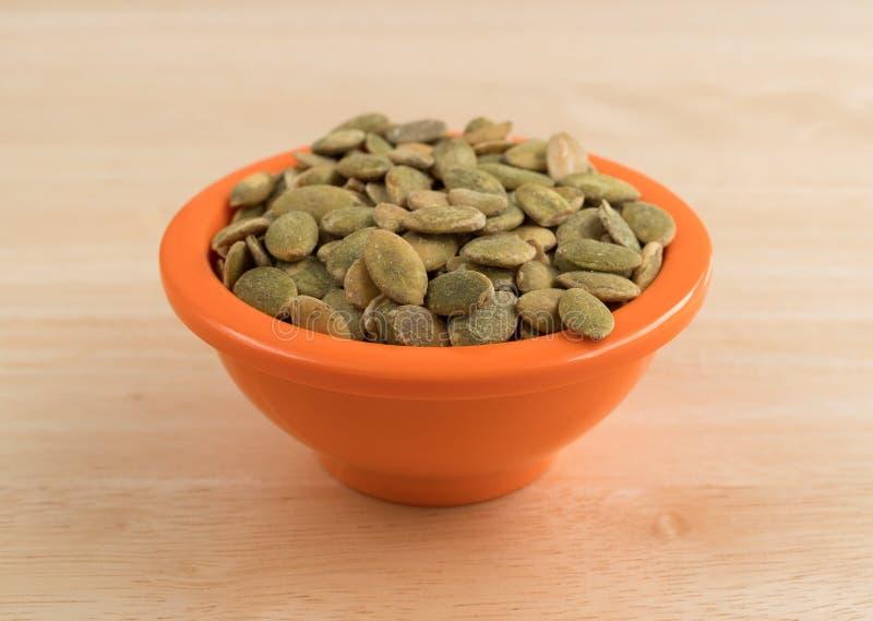 Orgânico seque sementes de abóbora roasted em uma bacia alaranjada pequena fotos de stock