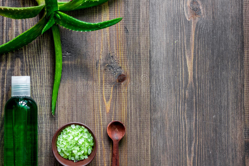 Organic aloe vera cosmetics. Aloe vera leafs, glass of aloe vera juice, spa salt on wooden background top view copyspace. Organic aloe vera cosmetics. Aloe vera stock photography