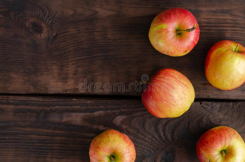 Organic apples on brown wooden background. Red apples royalty free stock image