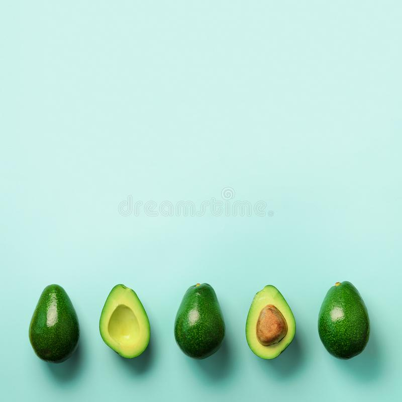Organic avocado with seed, avocado halves and whole fruits on blue background. Top view. Square crop. Pop art design stock photography