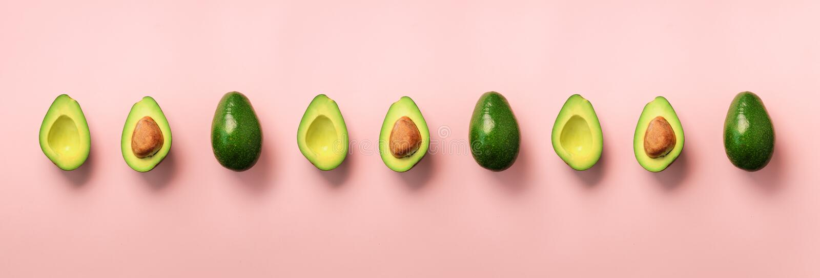 Organic avocado with seed, avocado halves, whole fruits on pink background. Top view. Banner, seamless pattern. Pop art design, cr royalty free stock images