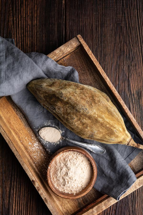 Organic baobab powder in a wooden bowl, healthy sport nutrition rich in vitamins and minerals stock photography