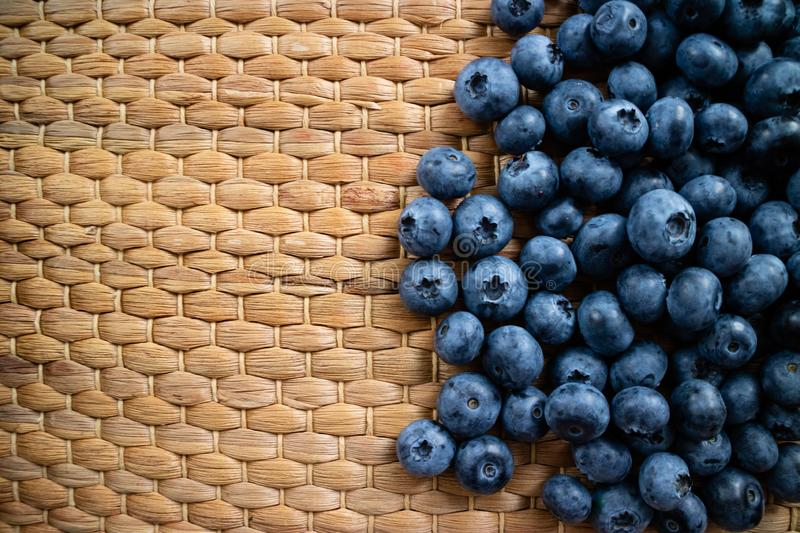 Organic blueberries on a wicker background with copy space royalty free stock photography