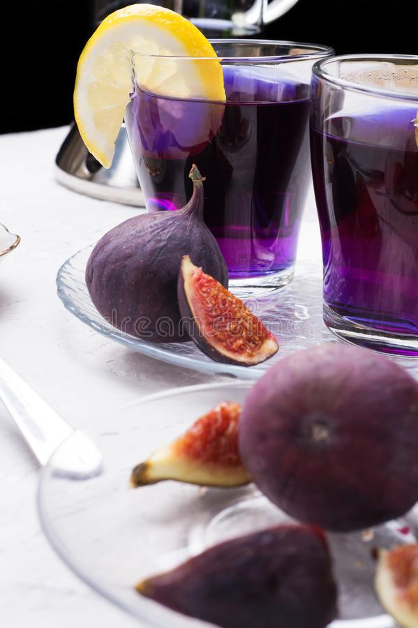 Organic Butterfly pea, clitoria or Blue pea flower herbal tea. Thai blue tea. served with lemon and fresh figs. close up royalty free stock photos