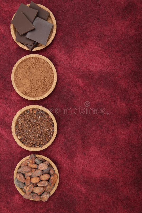 Organic cacao beans, cocoa powder, ground and chocolate on a red background with copy space for text. Flat lay, top view. royalty free stock image