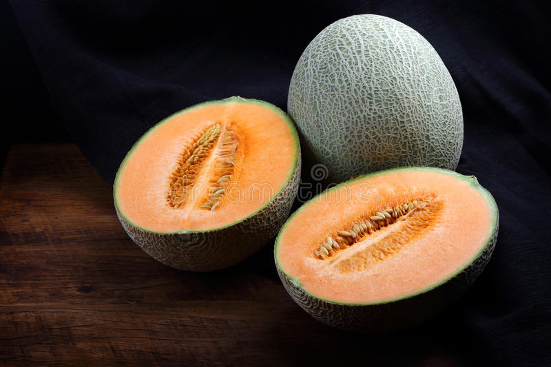 Organic cantaloupe on wooden table.  royalty free stock photography