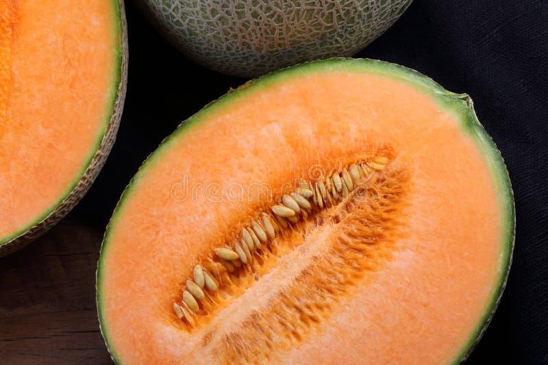 Organic cantaloupe on wooden table.  stock photos
