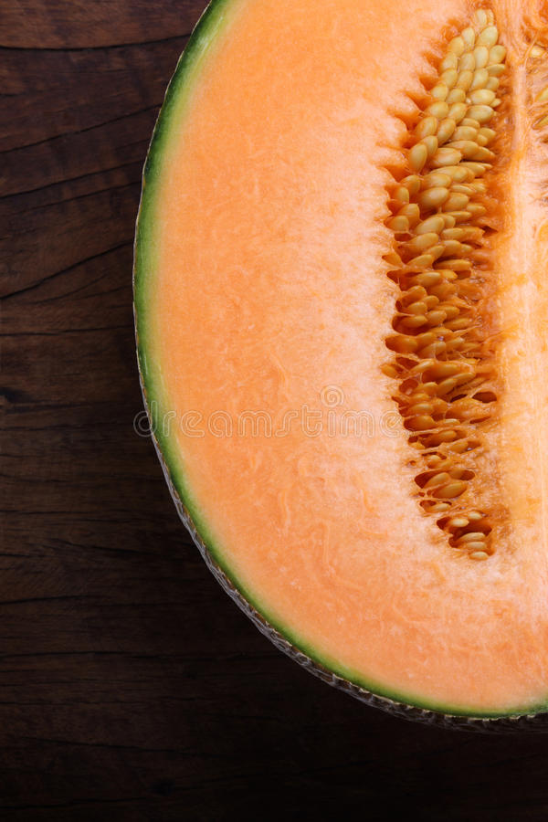 Organic cantaloupe on wooden table.  royalty free stock image