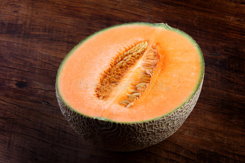 Organic cantaloupe on wooden table.  stock photography