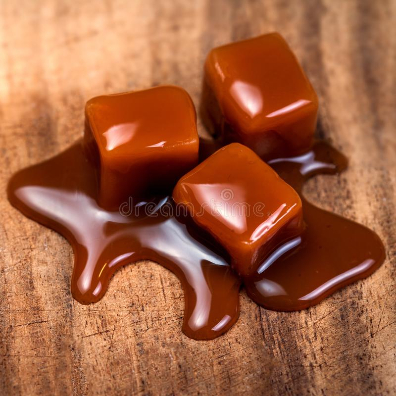 Organic caramel candies and caramel sauce on wooden table, Golden Butterscotch toffee caramels. Organic caramel candies and caramel sauce on wooden table stock photo