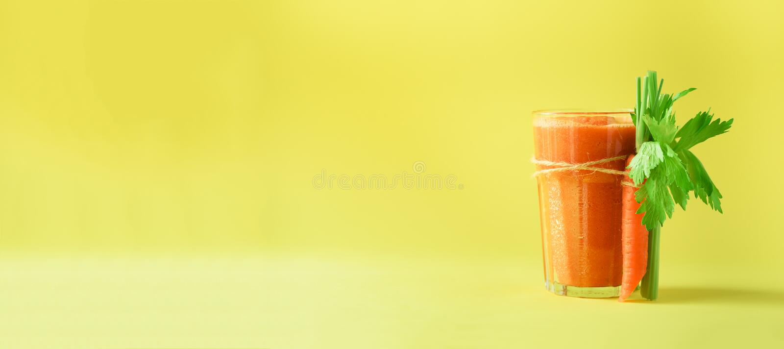 Organic carrot juice with carrots, celery on yellow background. Fresh vegetable smothie in glass. Banner. Copy space stock images