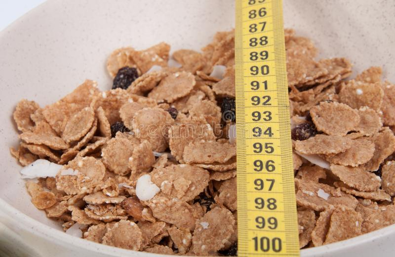 Organic cereal in beige bowl isolated. Organic cereal in beige bowl with tape measure Diet food royalty free stock photography