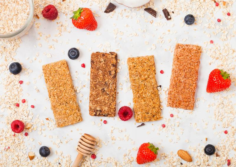 Organic cereal granola bar with berries with honey spoon and jar of oats on marble background. Top view. Strawberry, raspberry and royalty free stock images