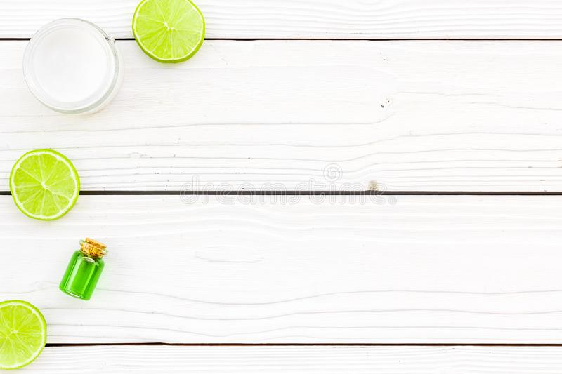 Organic citrus cosmetics for skin care. Lemon or lime oil and moisturising cream on white wooden background top view royalty free stock photos