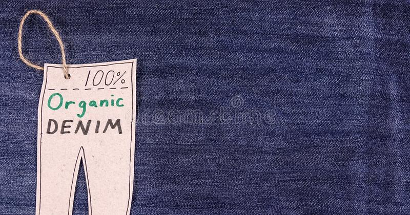 Organic clothes. Blue jeans denim background. Tag looking like pants. Copy space for text stock images