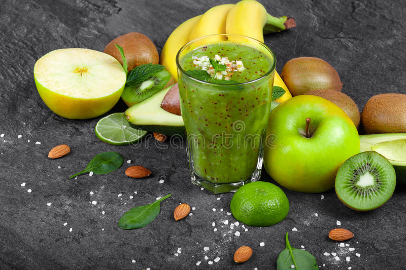 Various tropical fruits and green smoothie from kiwi on a dark gray background. Nutritious ingredients. royalty free stock images