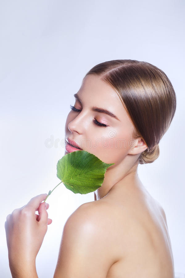 Organic cosmetic . Beautiful woman face portrait with green leaf , concept for skin care or organic cosmetics royalty free stock images